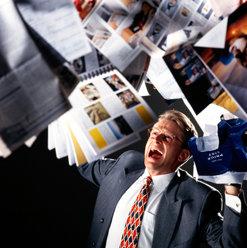 Man being deluged under increasing weight of paperwork